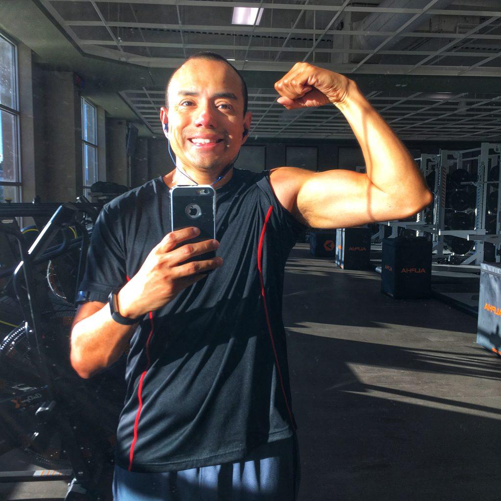Carlos flexing his left arm into a mirror.